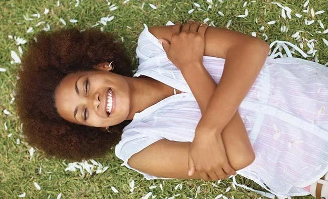 Young black woman relaxing on grass